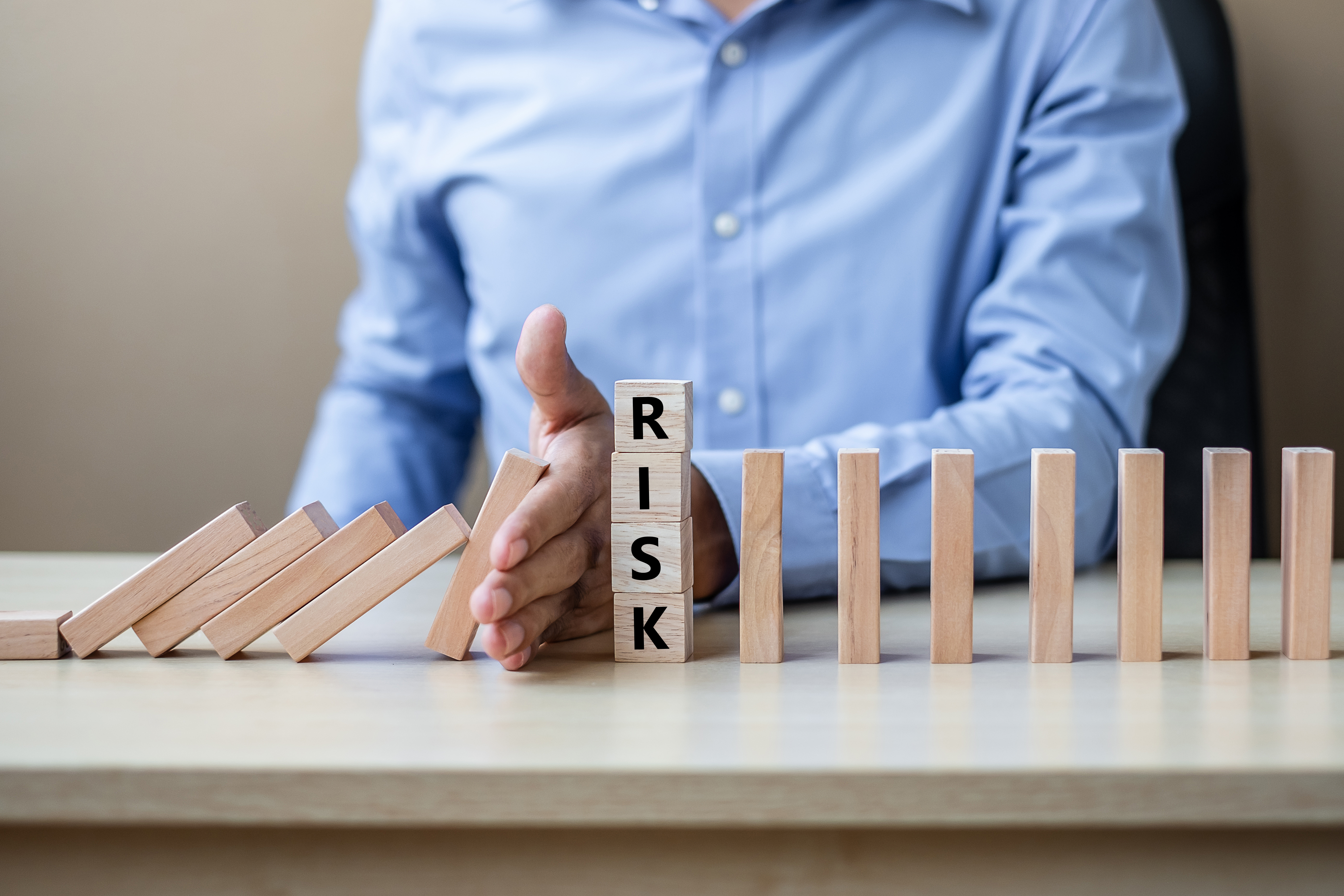 Businessman hand Stopping Falling wooden Blocks or Dominoes. Business, Risk Management, Solution, Insurance and strategy Concepts